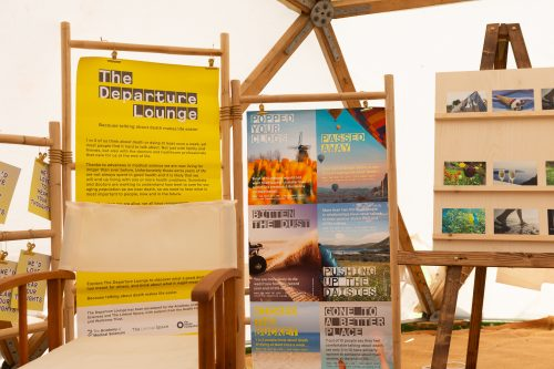 The Departure Lounge stand including posters of scenery with different phrases to describe death. There is a large yellow poster describing the exhibition. There is a collection of postcards featuring random images on a stand