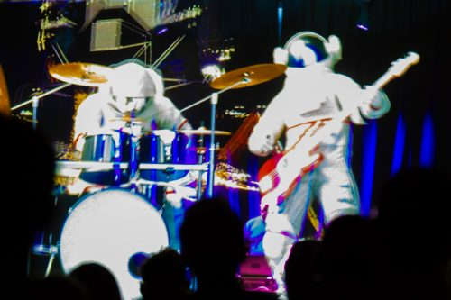 A holographic image of two spacemen in space suits play the drums on the left and an electric guitar on the right